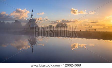 White Historic Windmill In Morning Fog