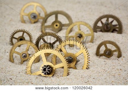 Time concept with a clockwork on the sand