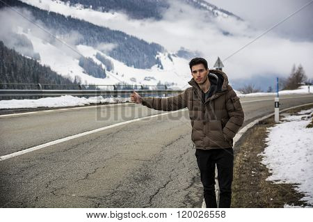Man thumbing a ride on roadside