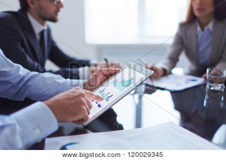 Human hand pointing at touchscreen in working environment at meeting