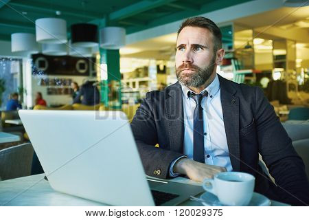 Pensive businessman sitting with his laptop in cafe