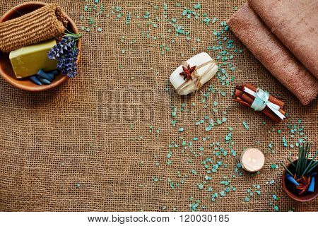 Assortment of aromatic products for relaxing spa or bath on hessian