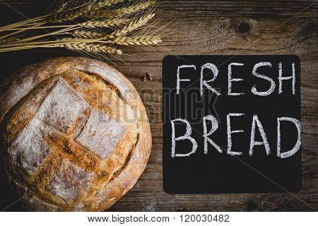 Bread loaf and golden wheat ears and black chalk board on textured wooden background, table top view food background