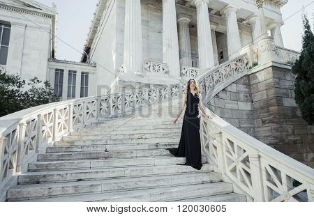 young lady in black dress on stone stairs