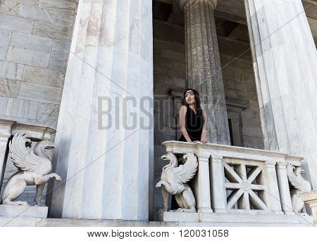 young lady in black dress on stone balcony with griffins
