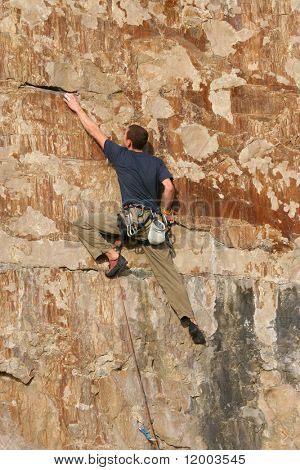 Rock climber ascending sheer cliff face