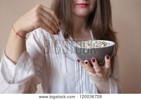 Beautiful young woman eating cereals