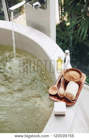 Spa decoration, natural organic products on a bathtube. Loofah, towel and frangipani flower.