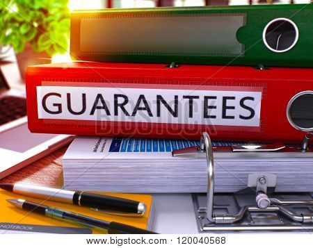 Guarantees on Red Ring Binder. Blurred, Toned Image.