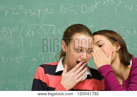 Two female students sharing a secret