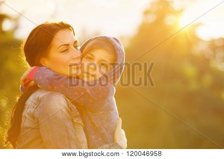 Portrait of beautiful mother with love hugging her precious daughter in bright yellow sunlight in the park, happy family life