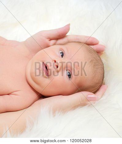 Newborn baby on white fur