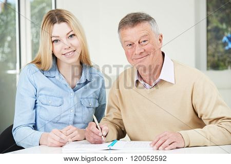Senior Man Playing Completing Sudoku Number Puzzle With Teenage Granddaughter