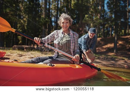 Happy Senior Woman In A Kayak At The Lake
