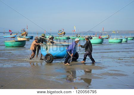 Fishermen pull a round plastic boat from the sea. Mui Ne, Vietnam