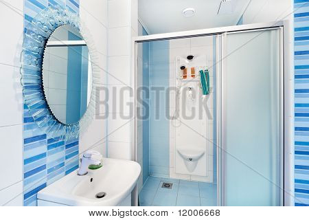 Modern Blue Bathroom Interior With Round Mirror And Shower Cubicle