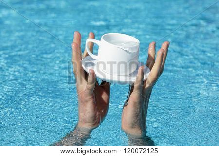two hands saving a cup and saucer containing some valuable liquid as a symbol of addiction, great value