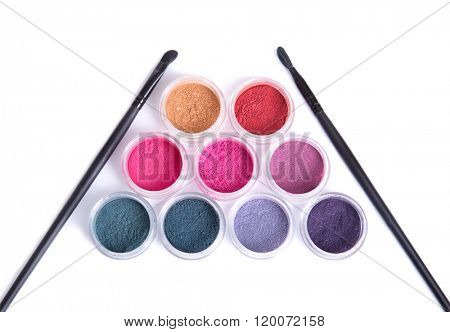 Top view of set of mineral eye shadows and makeup brushes, isolated on white background