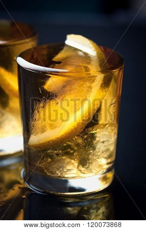 Alcohol cocktail with brandy whiskey lemon and ice in small glasses for party