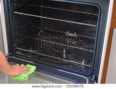 Housekeeper cleaning an oven