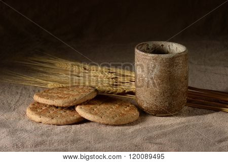 Wine and bread with wheat over vintage table cloth