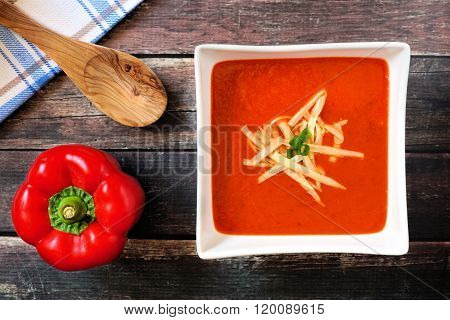 Red pepper soup in square bowl over wood