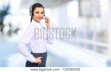 A Beautiful Young Woman By The Operator Of The Call Center With Headset On The Background Of The Off