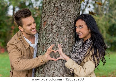 enamoured couple behind a tree