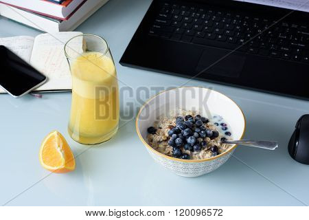 Healthy breakfast, muesli with berries and orange juice served on glass table, laptop, phone and books.
