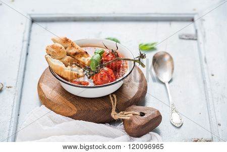 Italian tomato, garlic and basil soup Pappa al Pomodoro in metal bowl with bread on rustic wooden bo