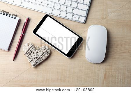 Computer peripherals with white wicker heart, notebook and mobile phone on light wooden table