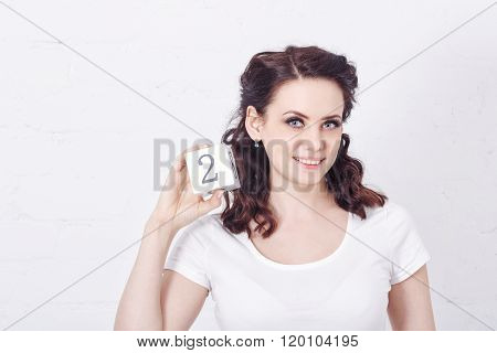 Girl In White T-shirt Holding Number Two.