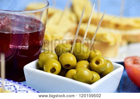 closeup of a glass with tinto de verano, a bowl with olives and a plate with tortilla de patatas, spanish omelet, served as tapas on sliced bread in the background