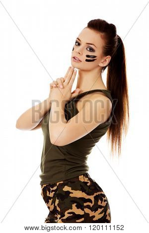 Young beautiful soldier woman doing gun gesture