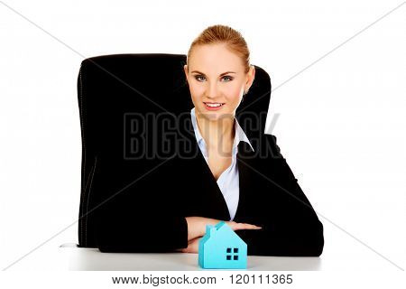 Business woman with blue paper house on the desk