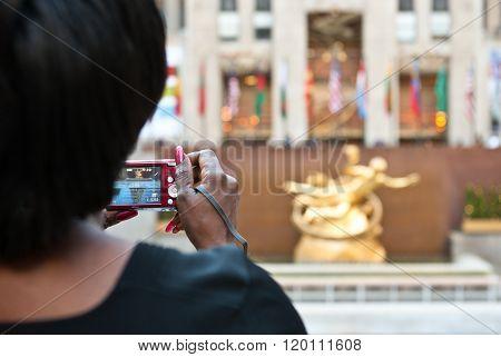 New York, U.S.A. - October 7, 2010: Manhattan, a woman taking a photograph in Rockefeller Center.