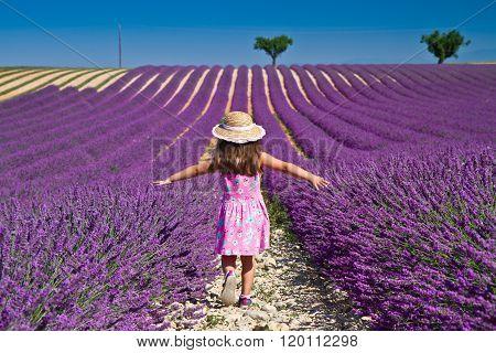 Girl in pink dress walking in lavender field