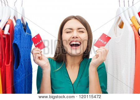 clothing, fashion, sale, shopping and people concept - happy woman showing tags on clothes at home wardrobe or shop