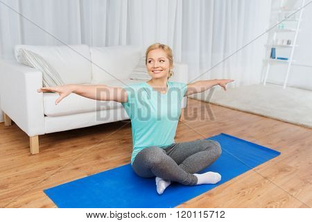 fitness, sport, people and healthy lifestyle concept - woman making yoga meditation in lotus pose on mat at home