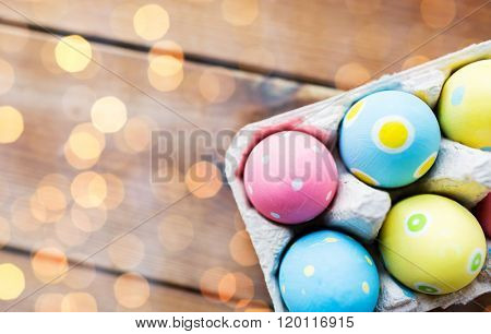 easter, holidays, tradition and object concept - close up of colored easter eggs in egg box or carton wooden surface with copy space over lights