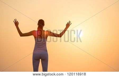 Young woman practising yoga in sunset