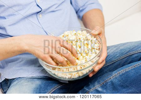 food, junk-food, unhealthy eating and people concept - close up of man eating popcorn at home