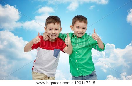 childhood, fashion, friendship, gesture and people concept - happy smiling little boys showing thumbs up over blue sky and clouds background
