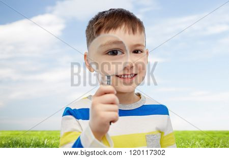 childhood, investigation, discovery, vision and people concept - happy little boy looking through magnifying glass over blue sky and green field background