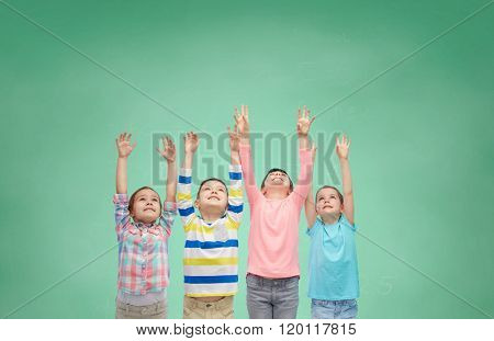 childhood, school, education, gesture and people concept - happy smiling children raising hands and celebrating victory over green school chalk board background