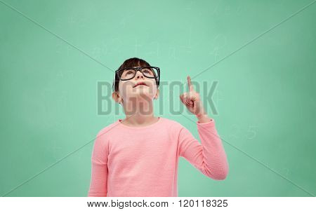 childhood, school, education, vision and people concept - happy little girl in eyeglasses pointing finger up over green school chalk board background