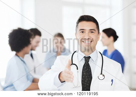 clinic, profession, people and medicine concept - happy male doctor over group of medics meeting at hospital prepared for handshake