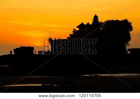 Silhouetted of Tanah Lot and sea waves in twilight Bali Indonesia.