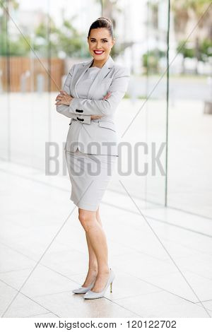 full length portrait of pretty young businesswoman with arms folded