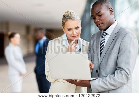 multiracial businesspeople using laptop computer in office